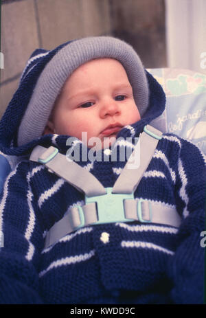 Baby boy toddler strapped in pushchair stroller - Stock Image