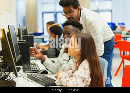 Teacher helping junior high students using computer in computer lab - Stock Image