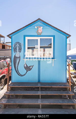 A tiny building with a mermaid mural in Petersburg, Mitkof Island, Alaska. Petersburg settled by Norwegian immigrant Peter Buschmann is known as Little Norway due to the high percentage of people of Scandinavian origin. - Stock Image