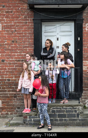 Presteigne, Powys, UK. A local family watching the annual carnival procession along the high street of this small town in mid-Wales - Stock Image