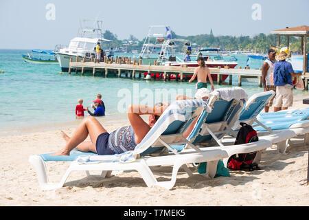 Tourist lying on the beach and enjoying the sun at West Bay Beach Roatan Honduras. - Stock Image