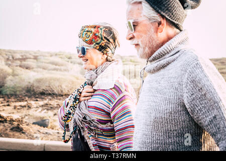 Aged coloured happy fashion hippy couple senior people in outdoor leisure activity together in couple - cold season and cheerful woman with husband in - Stock Image