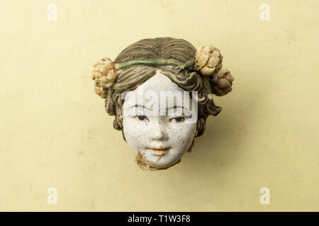 Detail of an old damaged porcelain chinese doll head. - Stock Image