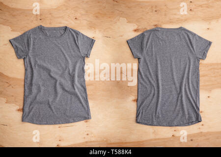Front and back of dark grey melange empty T-shirt on wooden background. Horizontal view. - Stock Image
