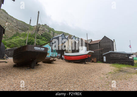 Fishing boats with the Hastings Net Shops, Fisherman black wooden huts at Hastings at Hastings, East Sussex, England , UK - Stock Image