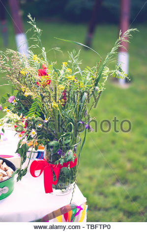 Bunch of plants and flowers standing on a table at - Stock Image