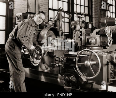 1940s SMILING MAN WORKING A LATHE MACHINE IN A FACTORY LOOKING AT CAMERA - i3890 HAR001 HARS SKILLS MACHINERY PRIDE REAR VIEW MANUFACTURING OCCUPATIONS LATHE CONTROLS FABRICATING PRESSES BACK VIEW MID-ADULT MID-ADULT MAN BLACK AND WHITE CAUCASIAN ETHNICITY FACTORIES HAR001 OLD FASHIONED - Stock Image