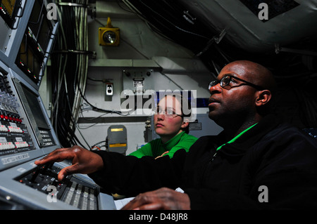 Sailors operate the ILARTS system aboard USS Carl Vinson. - Stock Image