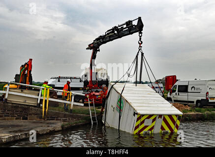 A Welfare container is lifted out of the Leeds and Liverpool canal near Haskayne following a act of vandalism with a JCB over night 23rd April 2019 - Stock Image