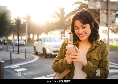 Happy young beautiful woman in green jacket using her smart phone walking on the city street at sunset - Stock Image