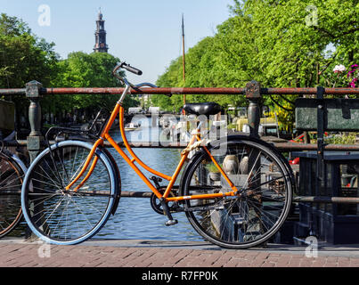 Traditional Dutch bike parked on a canal bridge in Amsterdam, Netherlands - Stock Image