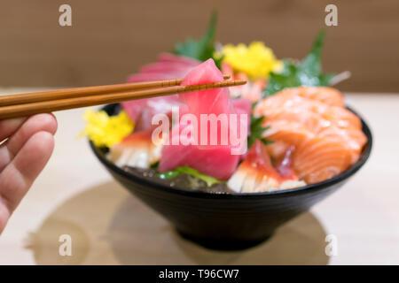 Chopsticks with Tuna sashimi with Mixed sliced fish sashimi on ice in black bowl. Sashimi Salmon Tuna Hamachi Prawn and Surf Calm set, raw fish, japan - Stock Image