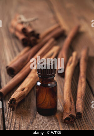 Glass bottle with essential oil of cinnamon, cinnamon sticks on a wooden background - Stock Image