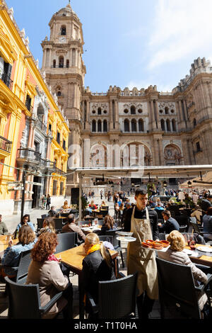 Malaga Spain; Tourists sitting at La Malaguena cafe overlooking Malaga Cathedral, Plaza del Bispo, Malaga Old Town, Andalucia Spain - Stock Image