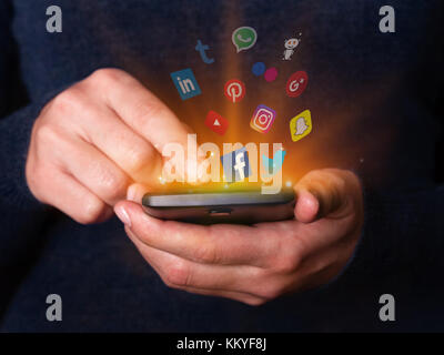 Woman hands holding using smartphone mobile phone checking social media network apps Facebook twitter YouTube Instagram - Stock Image
