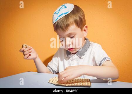 Cute Caucasian Jewish child with a kippah on his head touching the traditional matzo bread. Jewish Passover Pesach concept image. - Stock Image