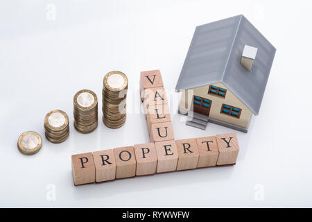 House Model And Stacked Coins Showing Property Value Concept On Reflective Desk - Stock Image