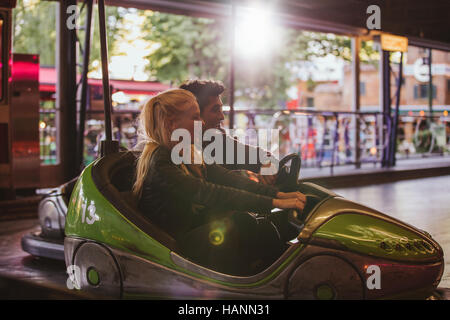 Happy young couple driving a bumper car at amusement park. Young man and woman riding bumper car at fairground. - Stock Image