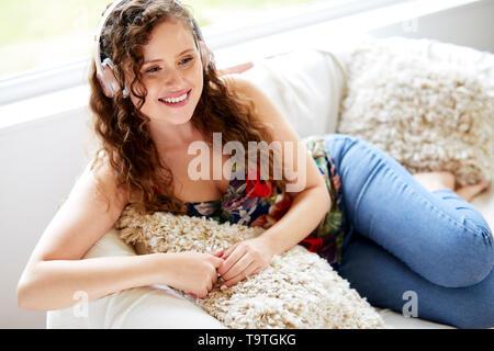 Girl relaxing listening to headphones - Stock Image