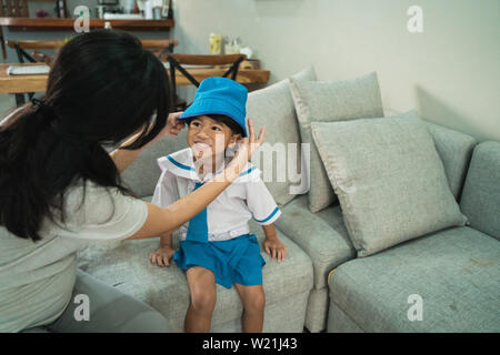kindergarten student wearing school uniform helped by her mom in the morning. back to school preparation - Stock Image