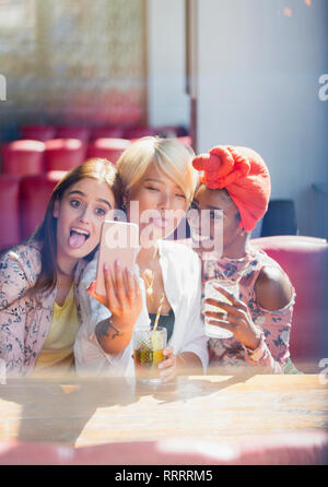 Silly, playful young women friends taking selfie with camera phone in cafe - Stock Image