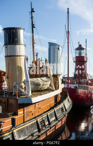 Two historic boats in Swansea Marina, the tug Canning and Lightship Helwick, owned by Swansea Museum, with The Tower at Meridian Quay behind. - Stock Image