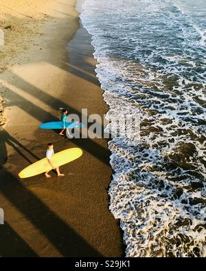 Male and a female surfer walk out to go surfing. Manhattan Beach, California USA. - Stock Image