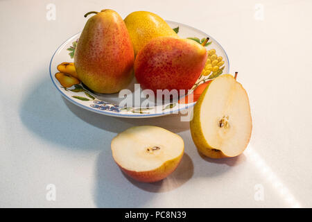 Three whole Bartlett pears, Pyrus communis, in a decorative plate, one pear cut in half. white background countertop. - Stock Image