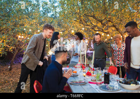 Friends arriving, sitting for dinner garden party - Stock Image