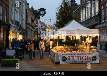Shoppers looking at a fudge stall on Winchester High Street with a Christmas tree and lights in the background - Stock Image