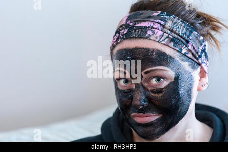 Woman doing beauty treatment having applied a black face mask looking at camera - Stock Image