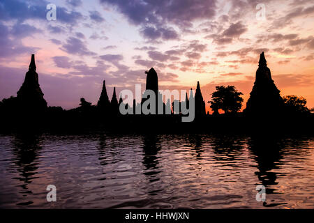 Landscape silhouette of Wat Chaiwatthanaram during sunset next to the Chao Phraya River is ancient temple famous - Stock Image