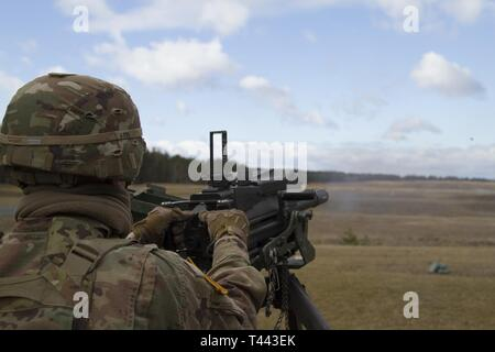 U.S. Army 1st Lt. Kevin A. Smith with the 2nd Battalion, 34th Armored Regiment, 1st Armored Brigade Combat Team, 1st Infantry Division launches a grenade down range with the MK-19mm grenade machine gun at Grafenwoehr Training Area, Germany, March 13, 2019. The Soldiers from 2-34 qualified on the range with a MK-19mm grenade machine gun and M2 .50-caliber machine gun. - Stock Image