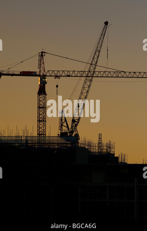 Tower cranes silhouetted on a construction site - Stock Image