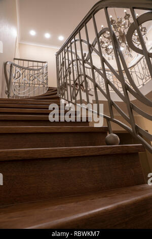 interior second light, stairs, wrought iron railings, chandelier - Stock Image