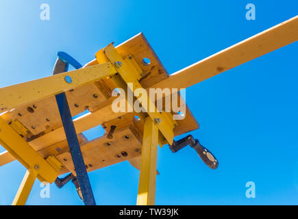 Close POV shot from below of a piece of wood, ready to be sawn, which is clamped in a portable workbench, outside against a blue sky. - Stock Image