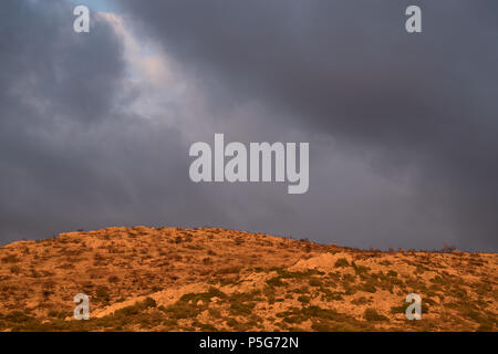 Greek mountain, Golden hour beautiful light with grey clouds, Saronida, Greece. - Stock Image