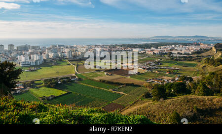 High perspective view of Greater Lisbon from Miradouro Aldeia dos Capuchos in Costa de Caparica, Almada. Palacio Pena in Sintra is visible in far righ - Stock Image