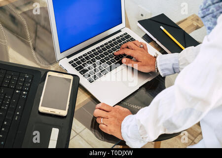 Close up and above view of woman hands typing on a keyboard and working with two laptop workstation computer at the office - manager and executive tec - Stock Image