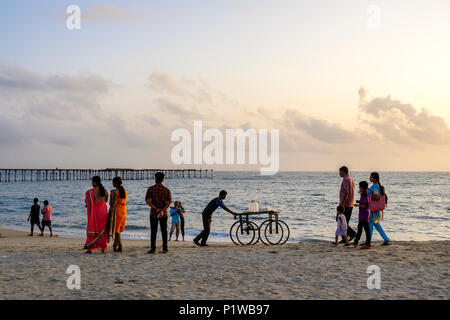 People enjoying an early evening walk on Alleppey (or Alappuzha) Beach, Kerala, India. - Stock Image
