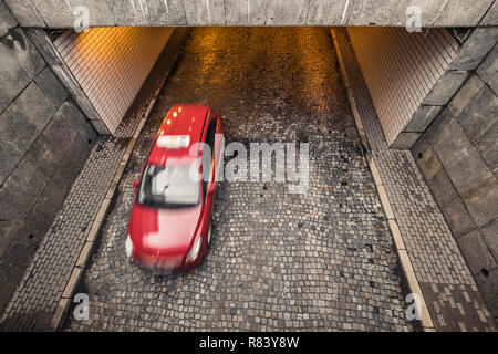 one red blurred passanger car leaves tunnel in Warsaw, Poland, overhead view - Stock Image