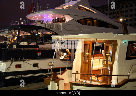 Luxury boats moored on the marina in the evening with the lights on. - Stock Image