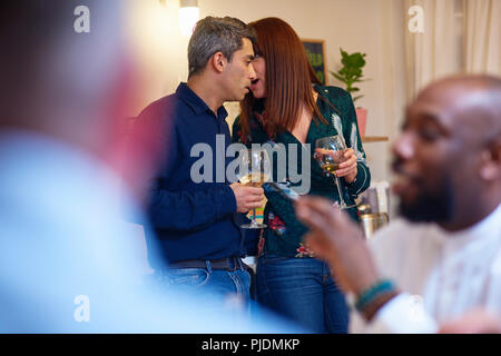 Friends talking, couple whispering at dinner party - Stock Image