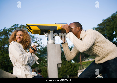 Tourist peering through large viewing binoculars - Stock Image