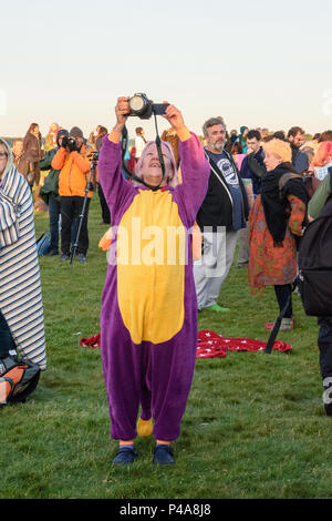 Stonehenge, Amesbury, UK, 21st June 2018,   Woman in an animal onesie taking a shot of the sun over the stones at the summer solstice  Credit: Estelle Bowden/Alamy Live News. - Stock Image