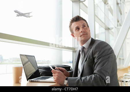 Businessman using laptop in airport - Stock Image