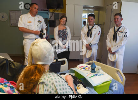 180830-N-OI558-0235 (Aug. 30, 2018) Sailors assigned to the Arleigh Burke-class guided-missile destroyer USS Dewey (DDG 105) and the Avenger-class mine countermeasures ship USS Scout (MCM 8) talk to a patient at the Children's Hospital of Orange County during Los Angeles Fleet Week (LAFW). LAFW is an opportunity for the American public to meet their Navy, Marine Corps and Coast Guard teams and experience America's sea services. During fleet week, service members participate in various community service events, showcase capabilities and equipment to the community, and enjoy the hospitality of L - Stock Image