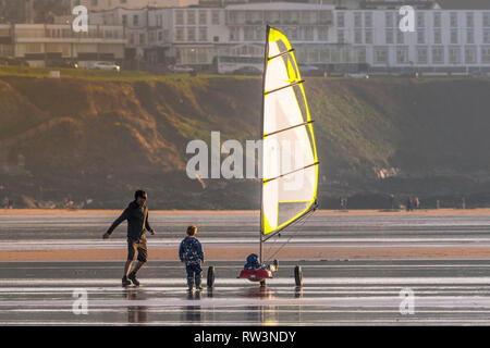 A father and his sons having fun with a sand yacht on Fistral Beach in Newquay Cornwall. - Stock Image