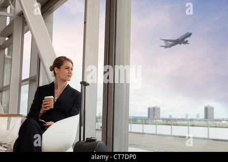 Businesswoman drinking coffee in airport - Stock Image