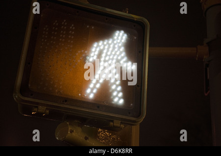 crosswalk sign showing walk at night - Stock Image
